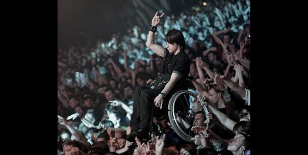 A kid in a wheelchair being held up at a Korn concert (Vodka_Vodka via Reddit)